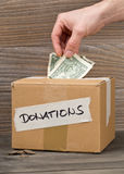 Man puts money into donations cardboard box with dollar banknote Stock Images