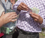 Man puts the money a  jar Royalty Free Stock Photo