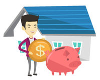 Man puts money into piggy bank for buying house. Royalty Free Stock Photography