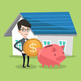 Man puts money into piggy bank for buying house. Royalty Free Stock Images