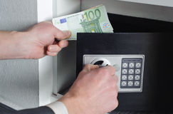 Man puts money in the safe. Man with one hand opens the safe  and the other holds money Stock Photos