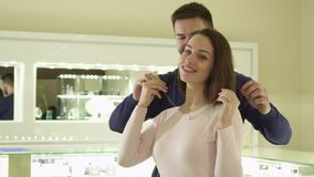 Man puts the necklace on his girlfriend`s neck at the boutique. Handsome bearded men putting necklace on his girlfriends neck at the boutique. Pretty caucasian Royalty Free Stock Photography