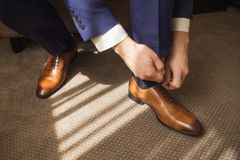 Man puts new brown modern shoes Stock Photos