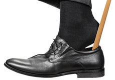 Man Puts On Black Shoe With Shoehorn Isolated