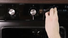 A man puts out the temperature twist the handle in a modern gas stove, close-up, modern gas cooker. A man puts out the temperature twist the handle in a modern stock footage