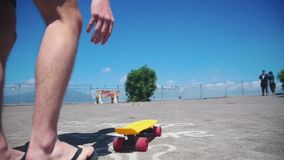 A man puts the penny board on the ground and standing on it. Mid shot stock footage