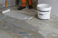 Man puts primer with roller on concrete floor. House under const Stock Image