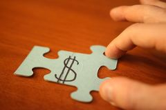 Man puts puzzles with image of dollar sign. Hands and pieces of puzzles with dollar close-up. royalty free stock image