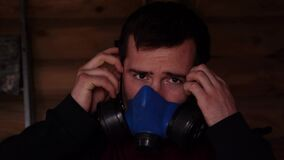 a man puts on a respirator on his face indoors