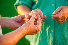 Man puts ring on woman. Hands of senior couple. It's never too late. Open your heart to love Stock Images