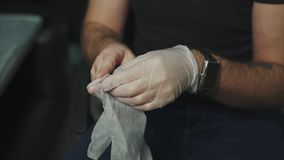 Man puts on rubber gloves on his tattoed hands