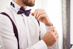 Man puts on shirt. Shallow depth of field. Focused on bow tie Royalty Free Stock Photo