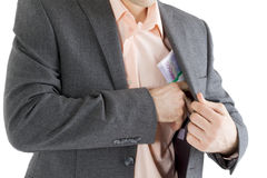 Man puts a stack of banknotes in a pocket Royalty Free Stock Photography