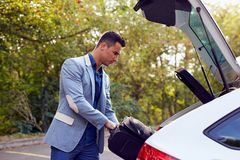 Man puts the suitcase in the trunk. Young man stands by the car and puts the suitcase in the trunk Stock Images