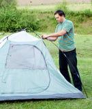A man puts a tent Royalty Free Stock Photos