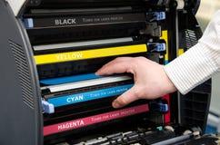 Man puts toner in the printer. Man hand puts toner in the printer Royalty Free Stock Image