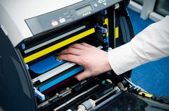 Man puts toner in the printer Royalty Free Stock Photography