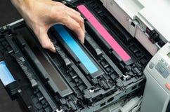 Man puts toner in the printer. Man hand puts cyan toner in the printer Stock Photos