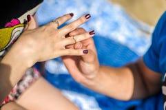 man puts  woman an engagement ring Stock Photos