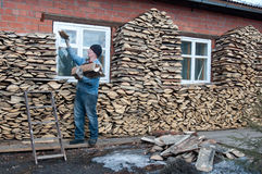 Stacking firewood. The man puts the wood to the wall at home. The standard way to build stacks - stack. Piling can effectively fill the space. An alternative way Royalty Free Stock Photo