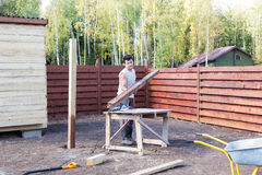 Man puts wooden beam on the bench Royalty Free Stock Photography
