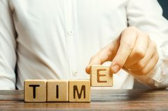 A man puts wooden blocks with the word Time. Concept of time management and proper distribution. Planning business and work. Business youth. Analysis of stock photos