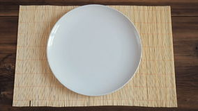 The man puts on wooden table from the old boards with napkin made of bamboo a white round dish and a metal fork stock footage