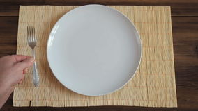 The man puts on wooden table from the old boards with napkin made of bamboo a white round dish and metal fork, and white stock video footage