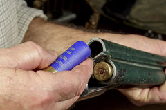 Man putting ammunition into an old double-barreled shotgun Royalty Free Stock Photos