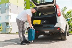 Man putting bags in car trunk. ready for car travel. Sunny morning royalty free stock photography