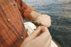 Man Putting Bait On Fishing Hook. Midsection of a man putting bait on fishing hook royalty free stock images
