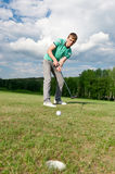 Man putting ball inside short putt Stock Image