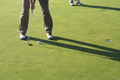 Man Putting Ball Into Hole Royalty Free Stock Images