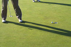 Man Putting Ball Into Hole Stock Images