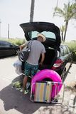 Man putting beach stuff in the car. A young caucasian man wearing a straw hat seen from behind putting in or taking out beach stuff from the trunk of his car Royalty Free Stock Photo