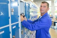 Man putting belongings in locker. Man putting belongings in a locker Royalty Free Stock Photography