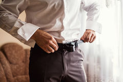 Man putting on a belt Royalty Free Stock Images