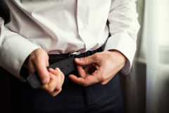 Man putting on a belt Royalty Free Stock Photo