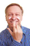 Man putting blob of lotion on his. Smiling elderly man putting blob of lotion on his nose stock photo