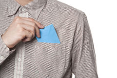 Man putting blue envelope in his shirt pocket Royalty Free Stock Images