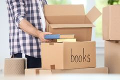 Man putting books into box indoors, closeup. Moving day royalty free stock photos