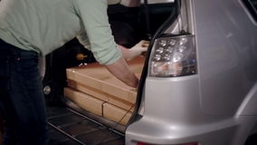 A man is putting boxes in the trunk of his car after shopping standing in the underground parking lot near mall. A man in a blue sweater and jeans is putting stock footage