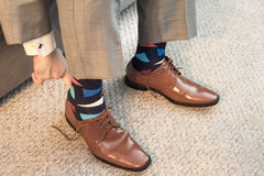 Man putting on brown dress shoes in formal wear with colorful socks. A man dressed in a suit putting on brown dress shoes. He& x27;s wearing colorful socks that Stock Photography