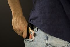 Man putting wallet with brazilian money inside the pocket royalty free stock photography