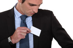 Man putting card into pocket Stock Images