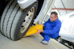 Man putting chock underneath wheel campervan Royalty Free Stock Images