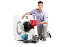 Man putting clothes into washing machine royalty free stock images