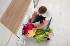 Man Putting Clothes In Washing Machine Stock Image