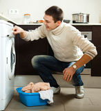 Man putting clothes into washing machine Stock Images