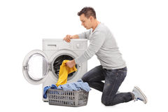 Man putting clothes in a washing machine Royalty Free Stock Photos